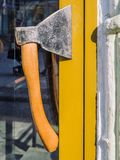 Door handle made of an ax. Creative design solution. Yellow door, the entrance to the cafe. Summer sunny day royalty free stock image