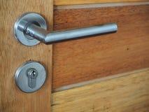 Door handle. Modern style door handle on natural wooden door Stock Photography