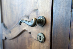 Door handle. Old vintage door handle on a wooden door Stock Photos