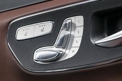Door handle with Power seat control buttons of a luxury passenger car. Brown leather interior with white stitching of the luxury m royalty free stock image
