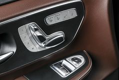Door handle with Power seat control buttons of a luxury passenger car. Brown leather interior with white stitching of the luxury m stock image