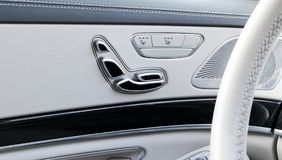 Door handle with Power seat control buttons of a luxury passenger car. White leather interior of the luxury modern car. Modern car Stock Photo