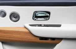 Door handle with power window control buttons of a luxury passenger car. White perforated leather interior with stitching and natu. Ral wood panel. Modern car stock photography