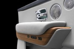 Door handle with power window control buttons of a luxury passenger car. White perforated leather interior with stitching and natu royalty free stock image