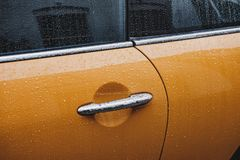A door handle of a wet yellow car royalty free stock photo