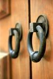 Door Handles. Close up of wrought iron door handles on ornate wooden door stock photos