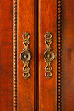 Door handles on cabinet. Ornate handles on wooden cabinet doors closeup Royalty Free Stock Photo