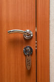 Door handles and key in keyhole. Door handles on wood wing of door and key in keyhole with numbered label Royalty Free Stock Image