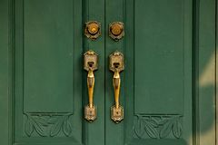 Door Handles Old brass on the green door royalty free stock photo