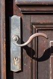 Door handles on wooden door. Old vintage door handles on a brown wooden door royalty free stock photos