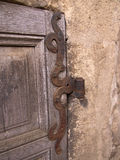Door hinge. Old, rusted door hinge connecting wood and stone Royalty Free Stock Photography