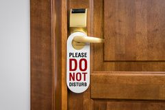 Door of hotel room with sign please do not disturb. Entrance door of hotel room with sign please do not disturb Royalty Free Stock Images