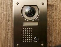 Door intercom on wood. Intercom with camera on wooden front door royalty free stock photo