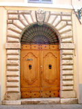 Door in Italy. A beautiful big closed wooden door in front of an old house in Italy Royalty Free Stock Photo