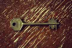 Door key on vintage wooden surface Royalty Free Stock Photos