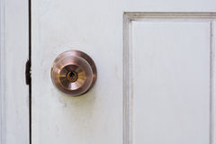 Door knob and keyhole on white wooden door Royalty Free Stock Photo