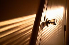 Door knob with light rays. Inside a home, a door with lights rays shining through a window Royalty Free Stock Photos