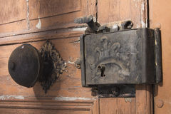 Door knob and lock. Old Latvian church wooden door with metal knob Royalty Free Stock Photo