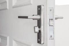 Door knob on the white door. Steel door knob on the white door Royalty Free Stock Image