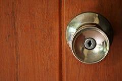 Door knob on wooden door. Door knob on wallpaper wooden door Royalty Free Stock Photography