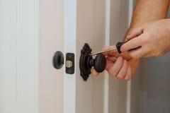 Door knobs, aluminum door white background. Installation of a lock at the door Stock Photo