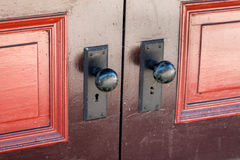 Door Knobs with Old Fashioned Key Lock. Brightly painted double door with old fashioned black door knobs and locks for skeleton keys Stock Photo