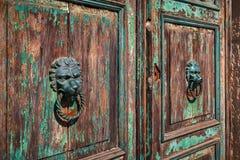 Door knobs in the shape of lion`s head on old wooden door. Royalty Free Stock Image