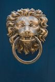 Door knocker. Traditional brass door knocker in the shape of a lion's head against a blue painted door Royalty Free Stock Image