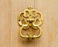 Door knocker. Golden door knocker on a wooden door Stock Photography
