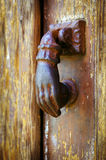 Door knocker. Close up on a rusty iron door knocker in a decaped old wooden door royalty free stock images
