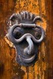 Door-knocker. Face-shaped door-knocker made of metal Stock Photography
