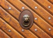 Door knocker on an antique door. Door knocker in the form of a lion`s head at an antique wooden door Stock Photography