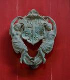 Door knocker 1. Brass door knocker on a red wooden door Royalty Free Stock Images