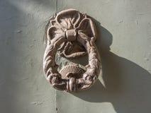 Door knocker on the front door of the Italian building. Door knocker on the front door made of wood of an Italian building royalty free stock photography