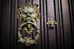 Door knocker. The door hammer is a fixture on the entrance door to the house. It is designed for guests to knock on it, tell the owners about their arrival and Royalty Free Stock Photos