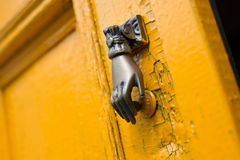 Door knocker knob closeup hand shape old vintage yellow orange Stock Photos