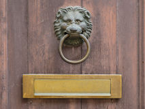 Door knocker and letterbox. Lion face shape door knocker and letterbox on ancient wooden door Royalty Free Stock Photos