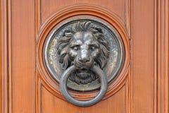 Door knocker lion. Brass lion knocker at wooden door Royalty Free Stock Images