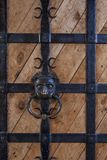 Door knocker lion head. Door knocker in the form of a lion`s head on the huge wooden gate of an ancient fortress royalty free stock images