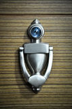 Door knocker with peep hole. Wooden doors and metal door handle Stock Image