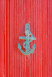 The door knocker in the shape of an anchor on a bright red backg Royalty Free Stock Photo