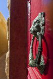 Door knocker. A door knocker in the shape of lions head on a red door of a Maltase house in the old city of Mdina Royalty Free Stock Photography