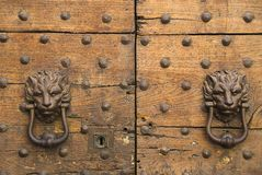 Door-knockers. Old door-knockers in the shape of lionheads at wooden door with rivets in Rome Royalty Free Stock Photo