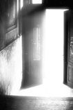 Door Into The Light. Open doorway in an old building with bright light coming out of it Conceptual artistic black-white photo Royalty Free Stock Photo
