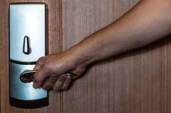 Door lock and hand. Door lock of wooden door being opening by hand stock image