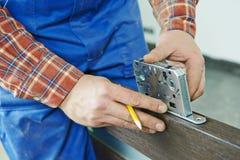 Door lock installation. Close-up carpenter hands with doorlock during lock process installation into wood door stock photography