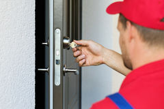 Door lock service - locksmith working. In red uniform stock photography