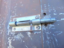 Door locked with bolt on old rusty garden house. Bolt locking the door of an old garden house Royalty Free Stock Image