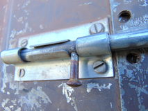 Door locked with bolt on old rusty garden house. Bolt locking the door of an old garden house Stock Image