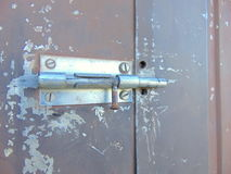 Door locked with bolt on old rusty garden house. Bolt locking the door of an old garden house stock photography